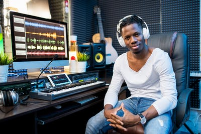 Happy young successful musician or producer in headphones sitting by workplace