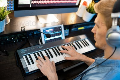 Hands of young man on piano keyboard during work over new music recording