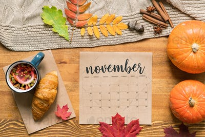 November calendar with hot drink and croissant, ripe pumpkins, leaves and spices