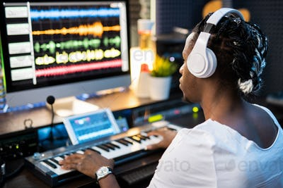 Young musician in headphones looking at sound waveforms on computer screen