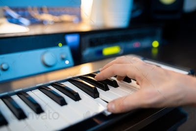 Hand of pianist pressing one of keys of piano keyboard while recording music