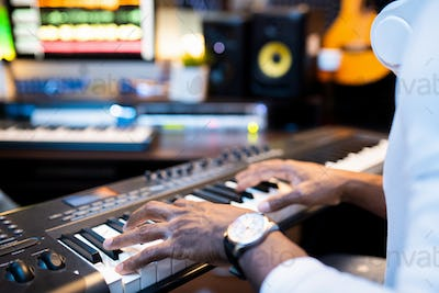 Hands of young African-american musician over keys of pianoboard working alone