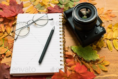 Photocamera, blank page of copybook with eyeglasses and pen and autumn leaves
