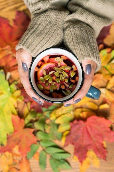 Female hands holding mug of hot herbal tea with lemon over autumn leaves