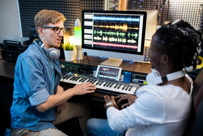 Multi-ethnic musicians in casualwear sitting by workplace in recording studio