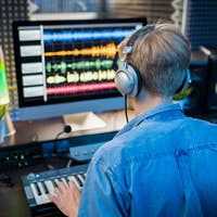 Rear view of young man in headphones making music by computer monitor