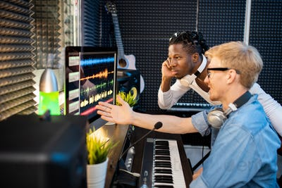 Young musicians looking at computer screen during discussion of sound waveforms