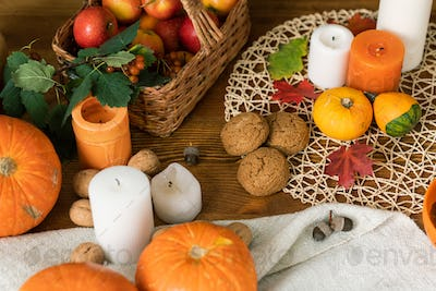 Composition of ripe pumpkins, candles, cookies, leaves and basket with apples
