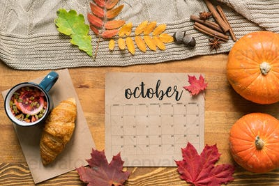 October calendar among fresh pastry with tea, ripe pumpkins, leaves and spices