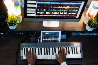 Human hands on keys of piano keyboard during process of recording new music