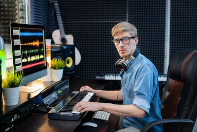 Young man with headphones looking at you while sitting in recording studio