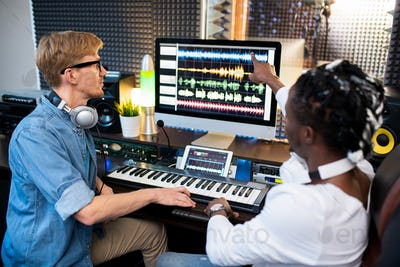 One of contemporary musicians pointing at sound waveform on computer screen