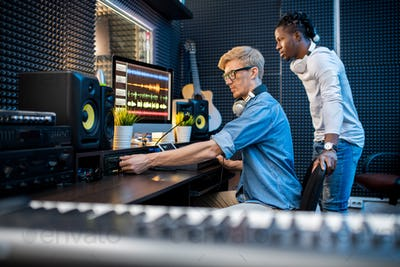 Young casual man adding volume while recording music with his African colleague