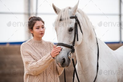Young brunette woman in white knitted woolen sweater standing by white racehorse
