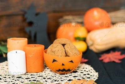 Halloween plastic bowl with cookies and three candles on white knitted napkin