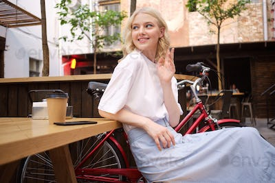 Beautiful flirty blond girl happily greeting someone resting with coffee in courtyard of cafe
