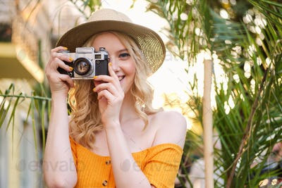 Portrait of pretty blond girl in hat happily taking photo on retro camera on city street