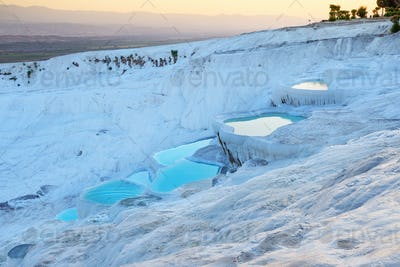 Pamukkale natural travertine terraces filled with blue water at sunset