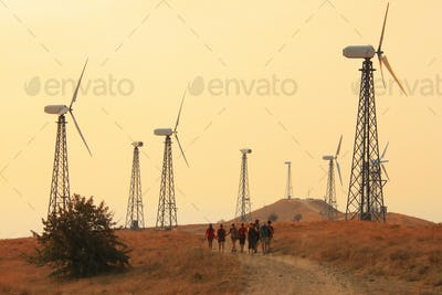 Group of people walking through fields with wind generators