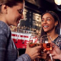 Three Women Making A Toast As They Meet For Drinks And Socialize In Bar After Work