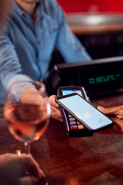 Close Up Of Woman Paying For Drinks At Bar Using Contactless App On Mobile Phone