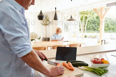 Senior Man Following Recipe On Digital Tablet As Wife Sits At Dining Room Table An Reads Magazine