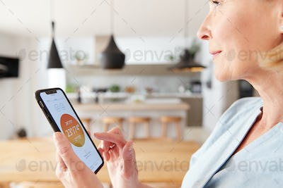 Mature Woman Using App On Digital Tablet To Control Central Heating Temperature In House