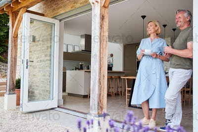 Senior Couple Standing And Looking Out Of Kitchen Door Drinking Coffee