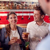 Male And Female Friends Meeting For Drinks And Socializing In Bar After Work