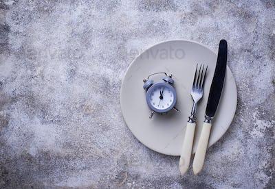 Grey alarm clock in empty plate.