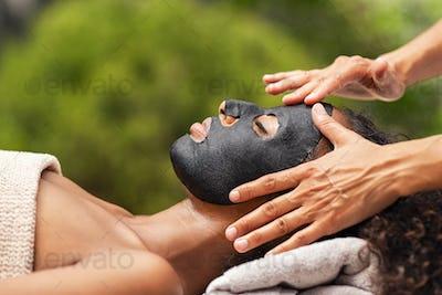 Purifying black beauty mask on woman face