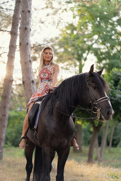 Young woman in a bright colorful dress riding a black horse