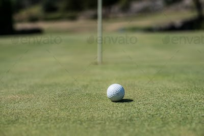 Golf field with white ball near the hole