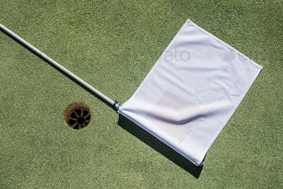 Golf field with empty hole and white flag