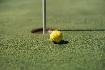 Golf field with yellow ball near the hole