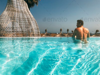 Man in a luxury swimming pool on the beach
