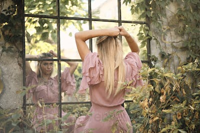Romantic blond girl in pink dress dreamily tying hair looking in reflection on window in old garden