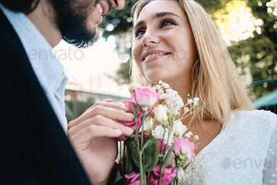 Close up attractive sensual blond bride with bouquet of flowers happily looking at groom outdoor