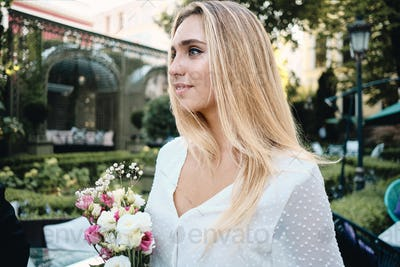 Romantic woman in white dress with bouquet of flowers sensually looking in garden of restaurant