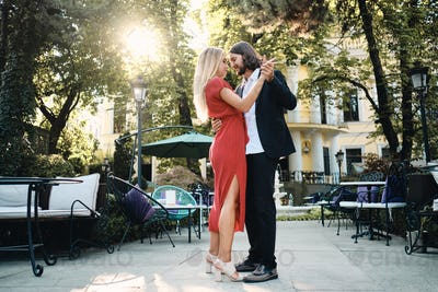 Young attractive romantic couple dreamily dancing on date in beautiful garden of restaurant