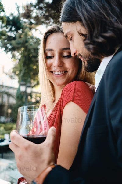 Happy romantic couple with glasses of red wine resting on date in beautiful restaurant outdoor