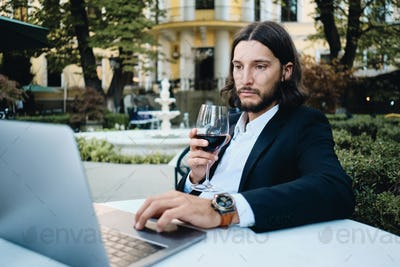 Handsome latin businessman with glass of wine thoughtfully working on laptop in restaurant outdoor
