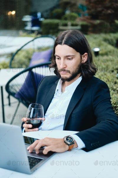 Confident latin businessman with glass of wine thoughtfully working on laptop in cafe outdoor