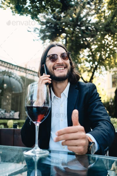 Handsome smiling latin man joyfully talking on cellphone resting with glass of wine in cafe outdoor