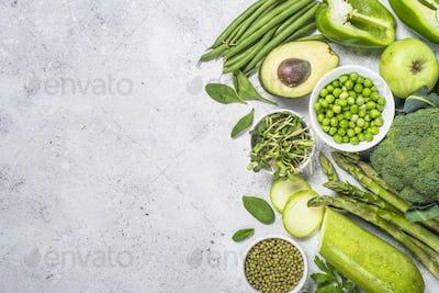 Green food assortment on light stone background