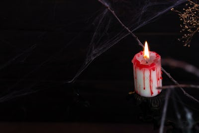 Antique candelabra with melting candle and spider web on black background. Copy space