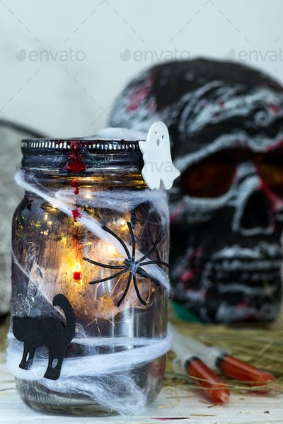 Jar filled with orange string lights in spooky room full in a black jar with a web and a spider on a