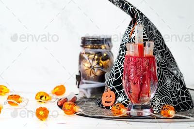 Halloween bloody glass with test tubes of tomato juice and Jar filled with orange string lights