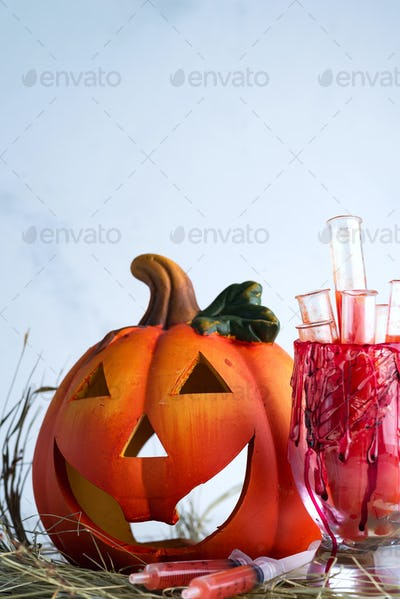Halloween bloody glass with test tubes of tomato juice and with pumpkin jack . Party drinks on dry