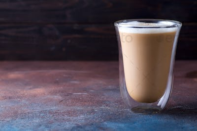 Glass cup of coffee latte on stone dark table
